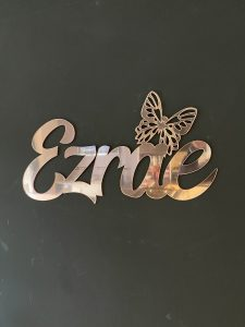 Ezrae Name sign with a butterfly in rose gold mirror acrylic