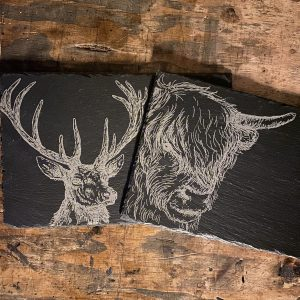 slate placemats laser engraved with a stag and highland cow by the altered state for ellie & hart